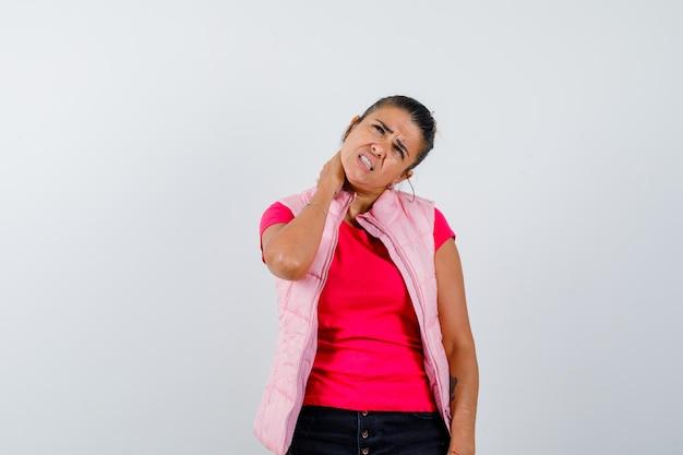 Frau leidet unter nackenschmerzen in t-shirt, weste und sieht erschöpft aus