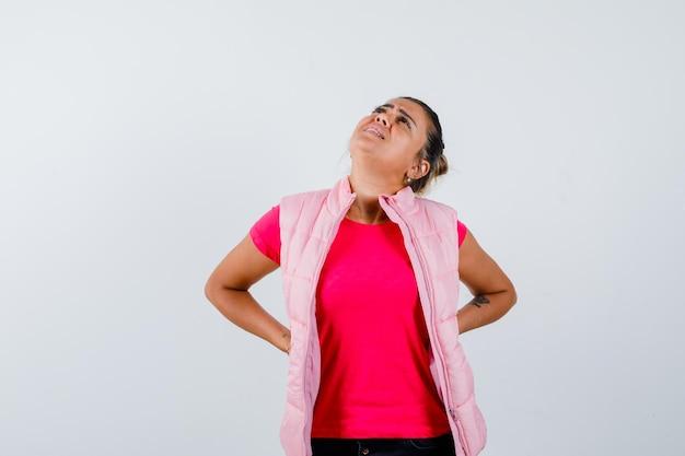 Frau leidet unter rückenschmerzen in t-shirt, weste und sieht müde aus