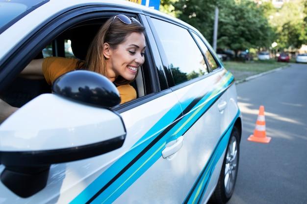 Frau lernt, ein auto zu fahren und rückwärts zu fahren