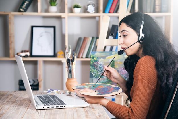 Frau lernt oder arbeitet, um zu hause online zu zeichnen.