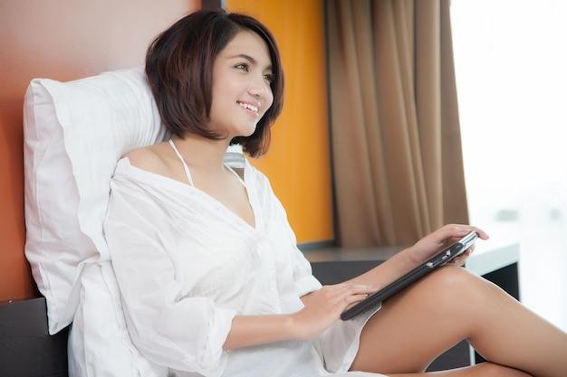 Frau liegend auf einem bett mit einem ipad tablet
