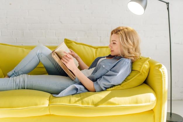 Frau liegend auf gemütlicher gelber couch und lesebuch