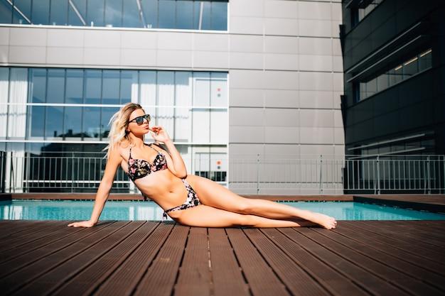 Frau liegt am rande des schwimmbades