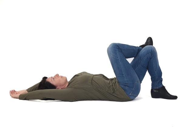 Frau liegt auf dem boden und schaut nach oben und die beine auf weißem hintergrund gekreuzt