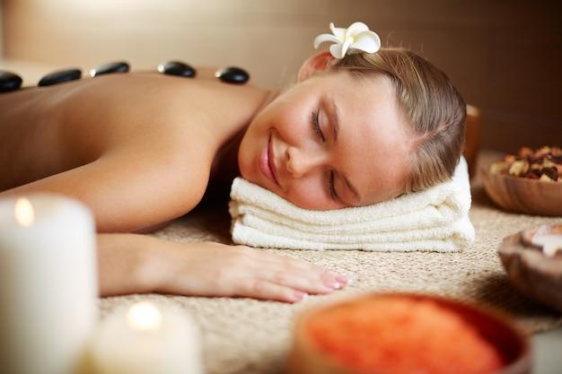 Frau liegt auf dem massagetisch mit heißen steinen auf dem rücken