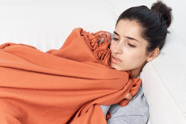 Frau liegt auf dem sofa mit einer decke bedeckt erkältung gesundheitsprobleme grippe