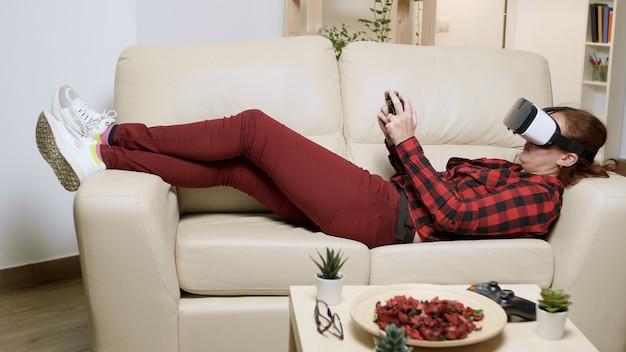 Frau liegt auf dem sofa mit vr-brille, um videospiele zu spielen. entspannte frau, die videospiele genießt.