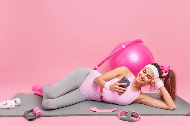 Frau liegt auf einer bequemen fitnessmatte und schaut sich videos über das smartphone an, gekleidet in sportbekleidung, übungen mit sportgeräten