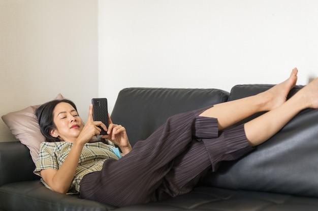 Frau liegt auf einer couch mit smartphone