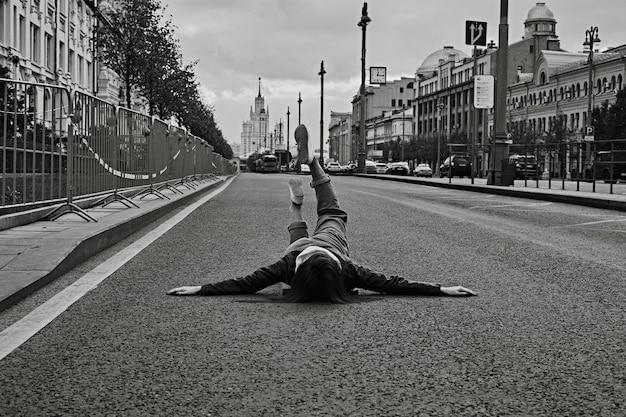 Frau liegt auf einer leeren asphaltstraße mit erhobenen beinen.