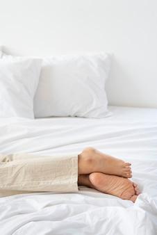 Frau liegt auf einer weißen matratze auf dem boden