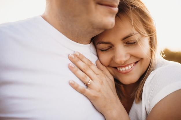 Frau liegt auf ihrem mann und umarmt ihn