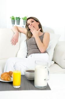 Frau liegt auf ihrem sofa, sie mietet, bevor sie frühstückt