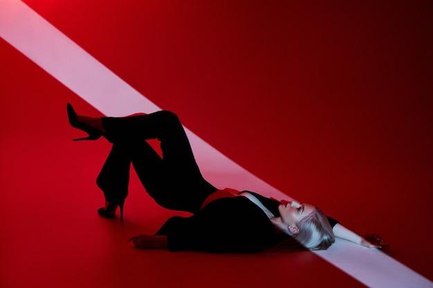 Frau liegt auf rotem hintergrund mit lichtstrahl auf gesicht. sexy nackte und selbstbewusste blonde frau in schwarzer jacke.