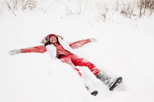 Frau liegt auf schnee