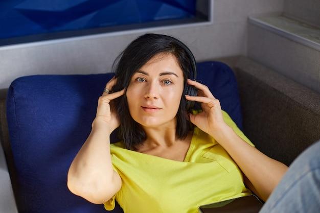 Frau liegt auf sofa und hört musik.
