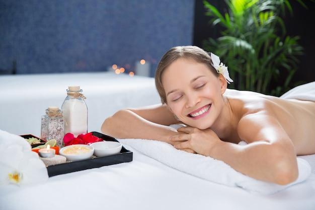Frau liegt im massageraum mit einem tablett mit aromen