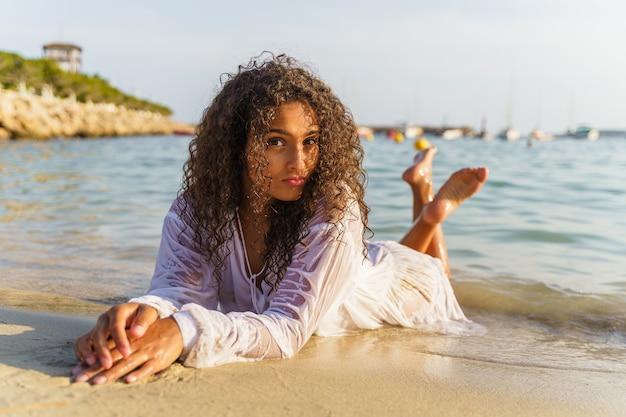 Frau liegt im sand und ist glücklich