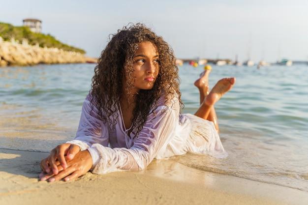 Frau liegt im sand und schaut auf den horizont