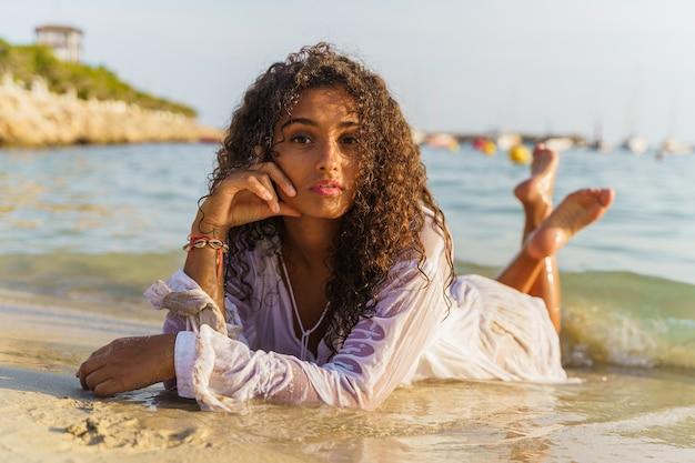 Frau liegt im sand und schaut geradeaus