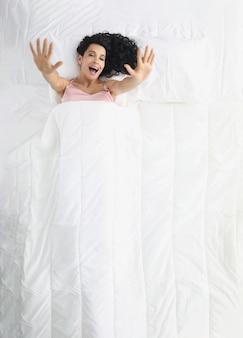 Frau liegt im weißen bett mit erhobenen armen und gähnender draufsicht