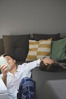 Frau liegt in der nähe des sofas mit smartphone in minimalistischer inneneinrichtung mit katze
