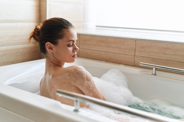 Frau liegt in einem bad mit sauberer haut der schaumresthygiene