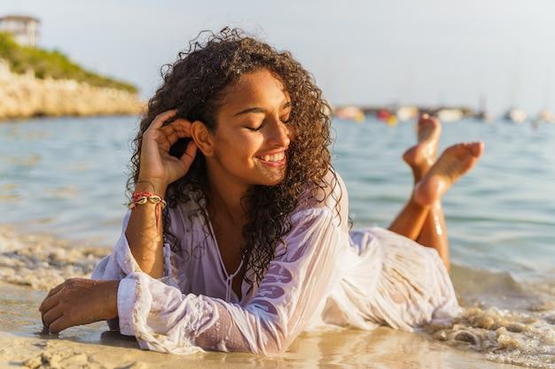Frau liegt mit geschlossenen augen im sand und lächelt