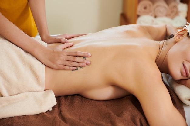 Frau liegt während der massage auf dem sofa