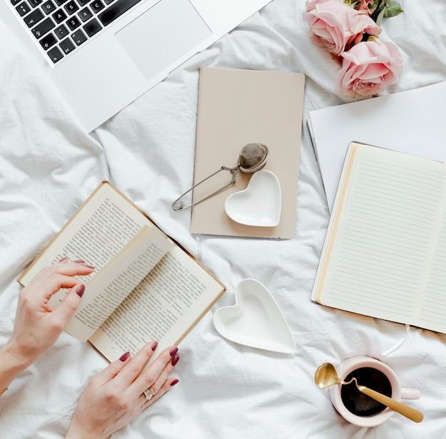 Frau liest an einem sonntagnachmittag einen roman auf ihrem bett bed