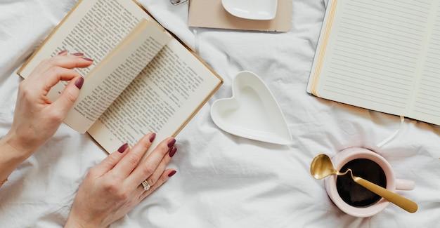 Frau liest an einem sonntagnachmittag einen roman auf ihrem bett