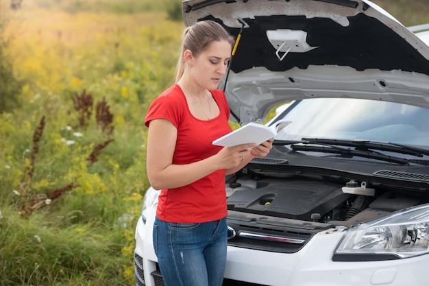 Frau liest bedienungsanleitung am kaputten auto auf der wiese