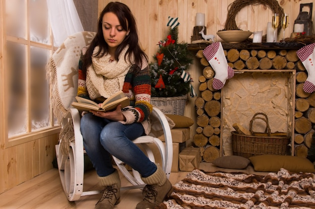 Frau liest buch im stuhl neben dem mantel in der rustikalen hütte zur weihnachtszeit