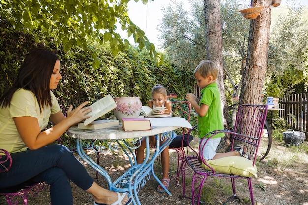 Frau liest buch mit kindern im garten