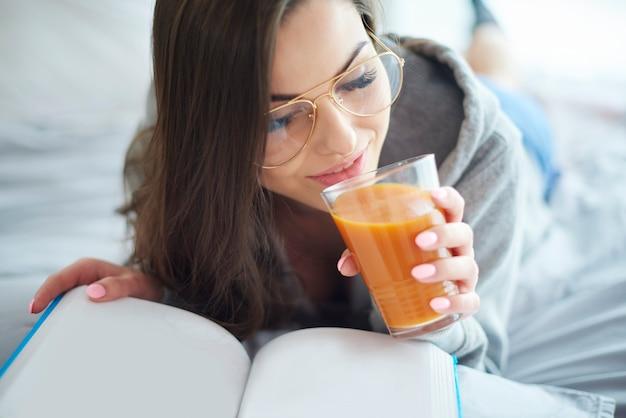 Frau liest buch und trinkt saft
