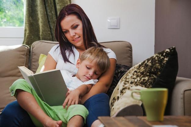 Frau liest buch zu junge sitzt auf sofa