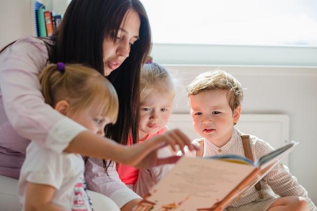 Frau liest buch zu kindern