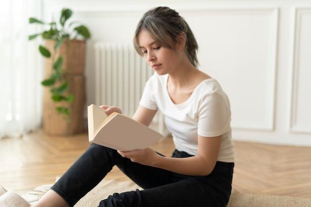 Frau liest ein buch auf dem boden sitzend