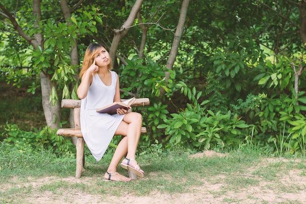 Frau liest ein buch auf einer hölzernen bank sitzt