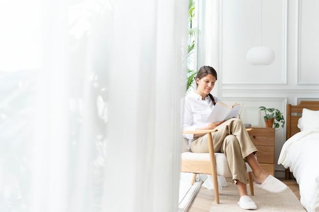 Frau liest ein buch in ihrem schlafzimmer