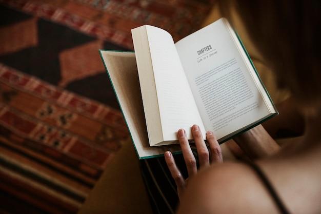Frau liest ein buch in ihrem wohnzimmer