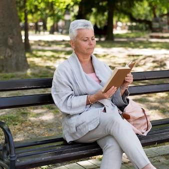 Frau liest mit mittlerer aufnahme