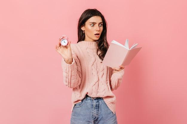 Frau liest schockierendes buch und hält rosa wecker. schuss der dame im pullover und in den jeans auf lokalisiertem hintergrund.
