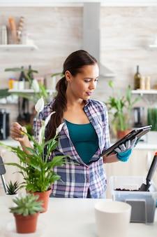 Frau liest über gartenarbeit auf tablet-pc in der heimischen küche