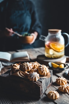Frau liest und heißer tee mit frischer grapefruit auf holztafel. gesundes getränk, öko, vegan.