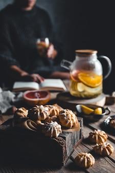 Frau liest und heißer tee mit frischer grapefruit auf holztafel