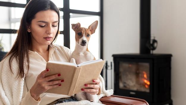Frau liest, während sie ihren hund hält