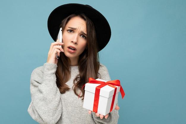 Frau lokalisiert über blaue hintergrundwand, die stilvollen schwarzen hut und grauen pullover hält, der geschenkbox hält, der auf smartphone spricht und kamera betrachtet.
