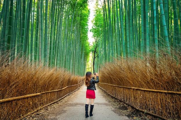 Frau machen ein foto am bambuswald in kyoto, japan.