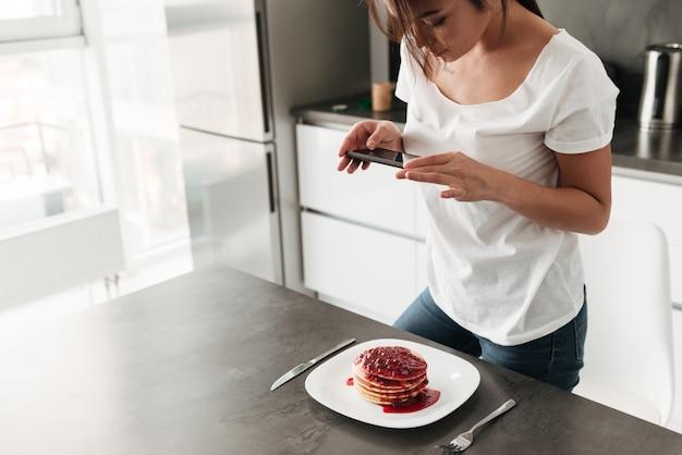 Frau machen foto von pfannkuchen mit dem handy.